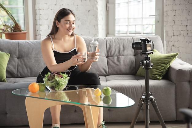 オーガニック。白人のブロガー、女性は、ダイエットと減量の方法をvlogで作成し、体をポジティブにし、健康的な食事をします。彼女のフルーツサラダの準備を記録するカメラを使用します。ライフスタイルインフルエンサー、ウェルネスコンセプト。
