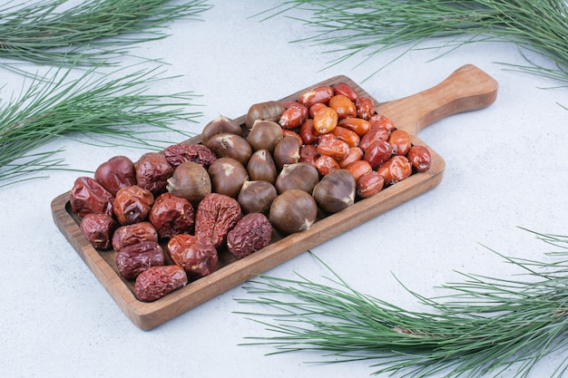 Organic chestnuts and silverberries on wooden board.