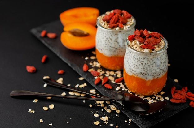 Organic chia seed pudding with goji berries, smashed fresh apricot and oat flakes on black slate board.