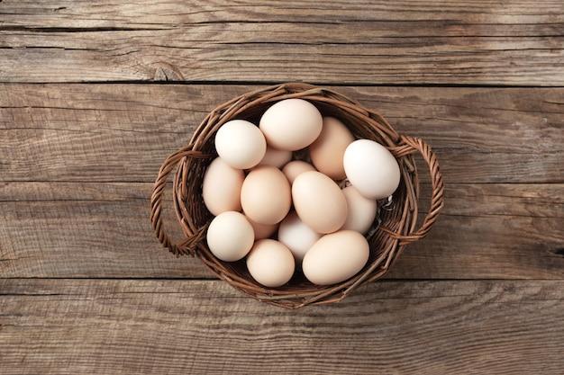나무 배경에 바구니에 유기농 닭고기 달걀입니다. 방목 및 목초지에서 자란 암탉의 계란으로 유기농 가정 개념