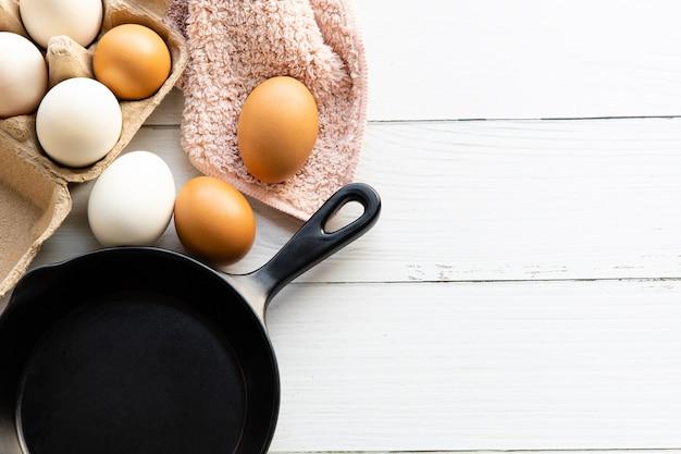 白い木製のテーブルに置かれた茶色の紙箱と黒い鍋の有機鶏卵朝食の材料。上面図とコピースペース。フラットレイ