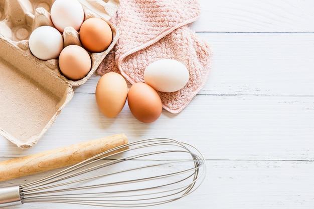 茶色の紙箱に入った有機鶏卵、白い木製のテーブルに置かれた泡立て器と麺棒。自家製パンを作るための原材料と設備上面図とコピースペース