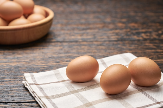 Organic chicken eggs in a wooden bowl on a kitchen table