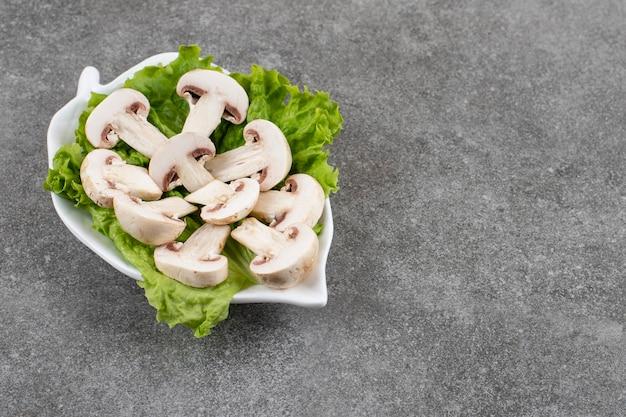 Funghi prataioli tagliati organici con lattuga sul piatto bianco.
