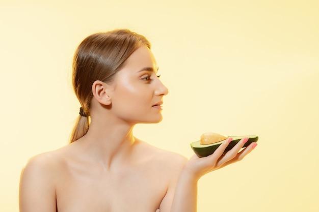 Органические крупным планом красивого женского лица с половиной авокадо