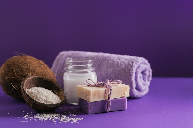 Organic coconut cosmetic oil and natural handmade soap with coconut and coco flakes on purple color
