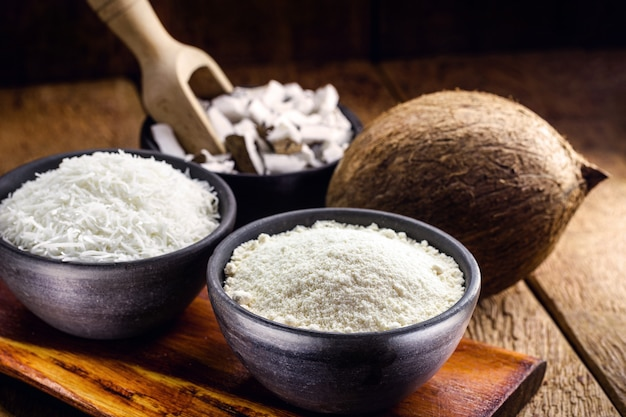 Органическая кокосовая мука на фоне тертого кокоса, кулинарные ингредиенты для фруктовых сладостей