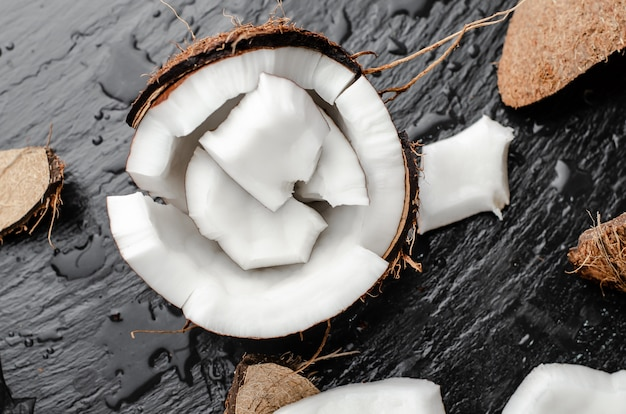 Organic coconut hlf with pieces on black slate stone background. healthy high fat foods concept.