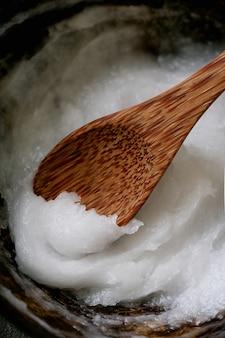 코코넛 숟가락에 코코넛 그릇에 유기농 코코넛 오일. 지속 가능성 개념. 확대.