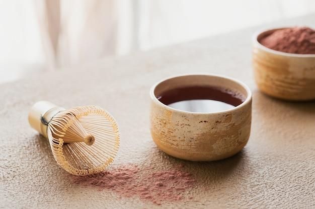 ベージュの背景に日本の道具を使ったオーガニックカラーのパウダーティー抹茶竹泡立て器。コンセプトベジタリアン健康飲料、飲料