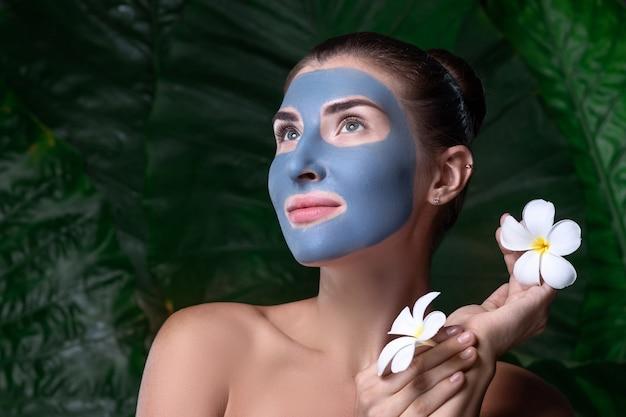 オーガニック化粧品。青い粘土のマスクを顔に、白い花を両手にした物思いにふける女性
