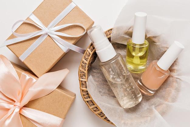 休日のための有機化粧品とギフト。フラットレイ、上面図透明ガラスポンプボトル、ブラシジャー、白い背景の紙かごの中の保湿美容液ジャー。ナチュラルコスメspa