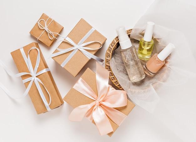 Органическая косметика и подарки к празднику. плоская планировка, прозрачная стеклянная бутылка с насосом, вид сверху, баночка с кистью, баночка с увлажняющей сывороткой в бумажной корзине на белом фоне. натуральная косметика spa