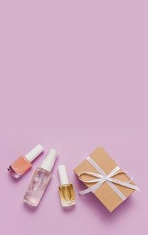 Органическая косметика и подарки к празднику. плоская планировка, прозрачная стеклянная бутылка с насосом, вид сверху, баночка с кисточкой, баночка с увлажняющей сывороткой на фиолетовом фоне. натуральная косметика spa