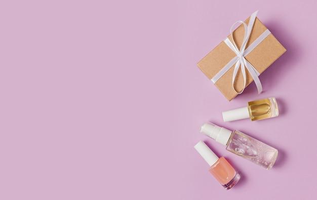 休日のための有機化粧品とギフト。フラットレイ、上面図透明ガラスポンプボトル、ブラシジャー、紫色の背景に保湿美容液ジャー。ナチュラルコスメspa