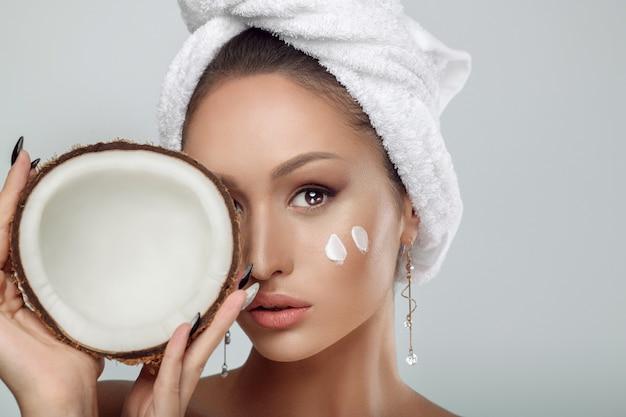 Органическая косметика. крупным планом портрет девушки с полотенцем на голове и мазки крема