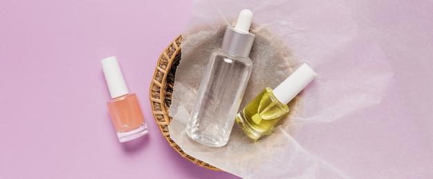 有機化粧品のパッケージデザイン。フラットレイ、上面図透明ガラスポンプボトル、ブラシジャー、紫色の背景の紙かごの中の保湿美容液ジャー。ナチュラルコスメspa