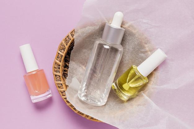Дизайн упаковки органической косметики. плоская планировка, прозрачная стеклянная бутылка с насосом, вид сверху, баночка с кисточкой, баночка с увлажняющей сывороткой в бумажной корзине на фиолетовом фоне. натуральная косметика spa