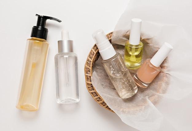 有機化粧品のパッケージデザイン。フラットレイ、上面図透明ガラスポンプボトル、ブラシジャー、白い背景の紙かごの中の保湿美容液ジャー。ナチュラルコスメspa