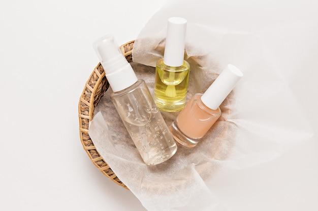 유기농 화장품 포장 디자인. 평평한 평지, 위쪽 투명 유리 펌프 병, 브러시 항아리, 흰색 배경에 있는 종이 바구니에 있는 보습 혈청 항아리. 천연화장품 spa