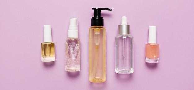 有機化粧品のパッケージデザイン。フラットレイ、上面図透明ガラスポンプボトル、ブラシジャー、紫色の背景に保湿美容液ジャー。ナチュラルコスメspa