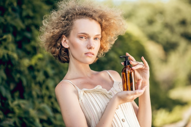 有機化粧品。手にエッセンシャル有機オイルのボトルを持っているきれいな女性