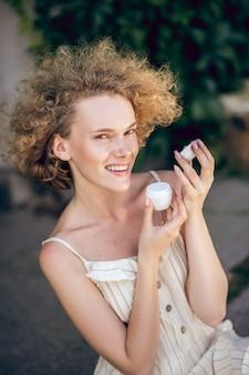 有機化粧品。手に有機フェイスクリームの瓶と階段に座っているきれいな女性