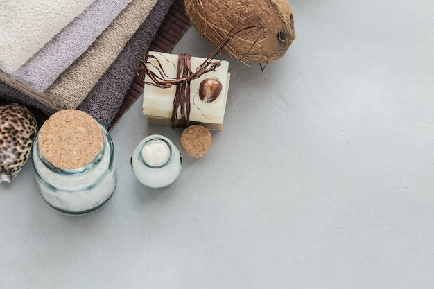 회색 표면에 코코넛 오일, 바다 소금, 수건 및 수제 비누가 들어간 유기농 화장품. 수제 페이셜 및 바디 마스크 또는 스크럽 용 천연 성분. 건강한 피부 관리. 스파 개념.