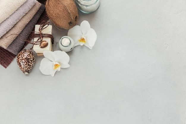 코코넛 오일, 바다 소금, 수건 및 회색 표면에 흰 난초 꽃과 수제 비누가 들어간 유기농 화장품. 수제 페이셜 및 바디 마스크 또는 스크럽 용 천연 성분. 건강한 피부 관리