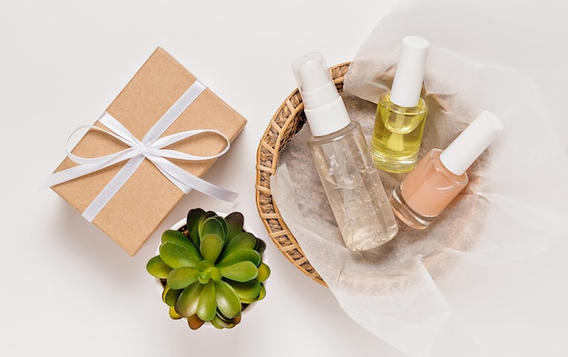 植物と休日の贈り物と有機化粧品。フラットレイ、上面図透明ガラスポンプボトル、ブラシジャー、白い背景の紙かごの中の保湿美容液ジャー。ナチュラルコスメspa