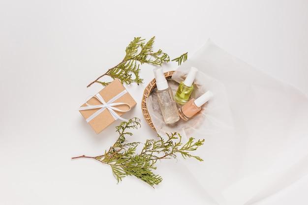 휴가를 위한 식물과 선물이 있는 유기농 화장품. 평평한 평지, 위쪽 투명 유리 펌프 병, 브러시 항아리, 흰색 배경에 있는 종이 바구니에 있는 보습 혈청 항아리. 천연화장품 spa