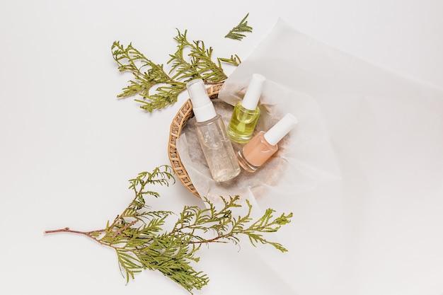 식물과 유기농 화장품입니다. 평평한 평지, 위쪽 투명 유리 펌프 병, 브러시 항아리, 흰색 배경에 있는 종이 바구니에 있는 보습 혈청 항아리. 천연화장품 spa