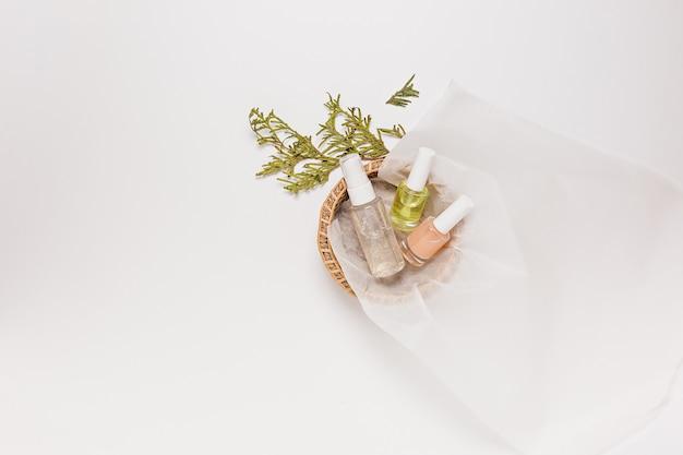 Органическая косметика с растениями. плоская планировка, прозрачная стеклянная бутылка с насосом, вид сверху, баночка с кистью, баночка с увлажняющей сывороткой в бумажной корзине на белом фоне. натуральная косметика spa