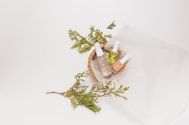 植物と有機化粧品。フラットレイ、上面図透明ガラスポンプボトル、ブラシジャー、白い背景の紙かごの中の保湿血清ジャー。ナチュラルコスメspa