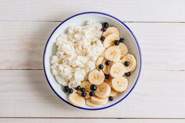 Органический творог с бананом для здорового завтрака. белый деревянный стол. вид сверху
