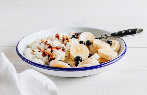 Органический творог с финиковым сиропом и бананом для здорового завтрака.