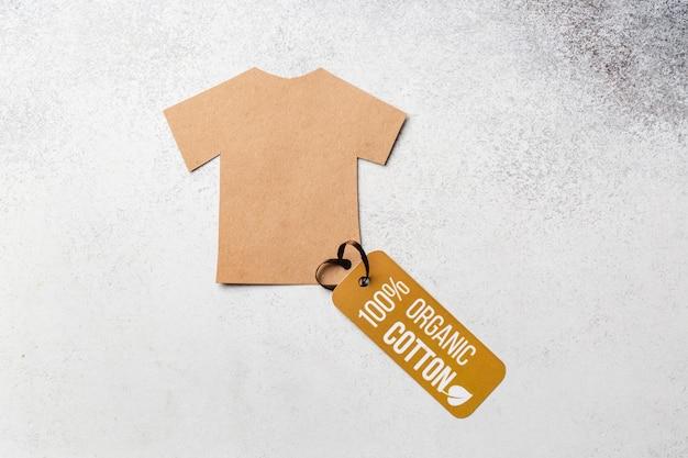 ラベルの付いたオーガニックコットンの服のコンセプト。ペーパークラフトのtシャツ。エコ衣類。高品質の写真
