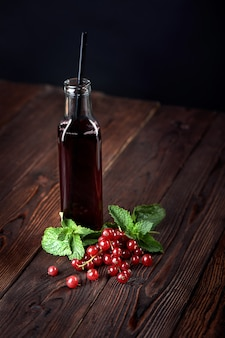 Organic cranberry juice in bottles with berries on wooden background