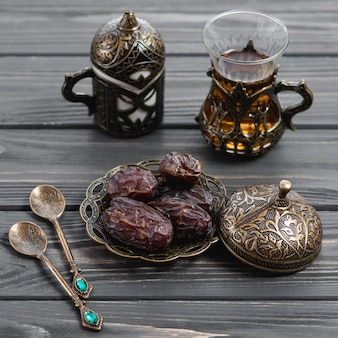 An organic dates on toreutic engraved artistic metal work plate and tea glass on wooden table