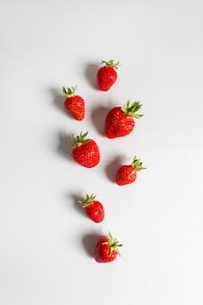 灰色の背景、平面図、フラットの有機おいしいイチゴ果実シームレスパターンが横たわっていた。夏の構図