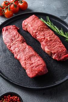 黒いプレート上の有機デンバーステーキ、灰色の石の表面の背景の側面図上のハーブトマトペッパーコーンと霜降り牛肉は、垂直方向の選択的な焦点を閉じます。