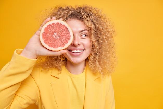 有機ダイエットの概念。喜んでいる巻き毛の女性は、グレープフルーツの半分の笑顔で目を覆い、フレッシュジュースやスムージーを脇に置いて、テキスト用の黄色い壁のコピースペース領域にポーズをとる