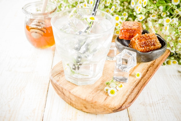 Organic diet detox summer beverage, infused water drink with camomile and honey, on white wooden table, with chamomile flowers and honey in a jar. copy space