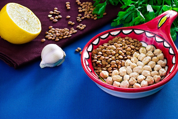 Organic diet food for healthy nutrition. ingredients for cooking vegetarian soup or stew. chickpea, lentil, lemon, parsley and garlic background