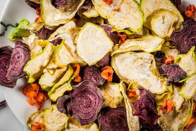 有機ダイエット食品。ビーガンダイエット。乾燥野菜。ビート、ニンジン、ズッキーニのホームチップ。新鮮な野菜を添えた白い大理石のテーブルの上。ビューを閉じる