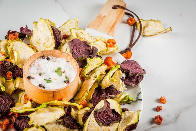有機ダイエット食品。ビーガンダイエット。乾燥野菜。ビート、ニンジン、ズッキーニのホームチップ。新鮮な野菜を添えた白い大理石のテーブルの上。コピースペース