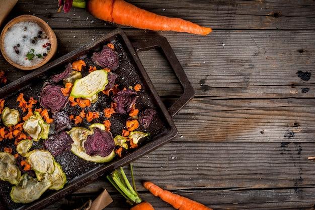 有機ダイエット食品。ビーガンダイエット。乾燥野菜。ビート、ニンジン、ズッキーニの自家製チップ。古い木製の素朴なテーブル、新鮮な野菜。 copyspaceトップビュー