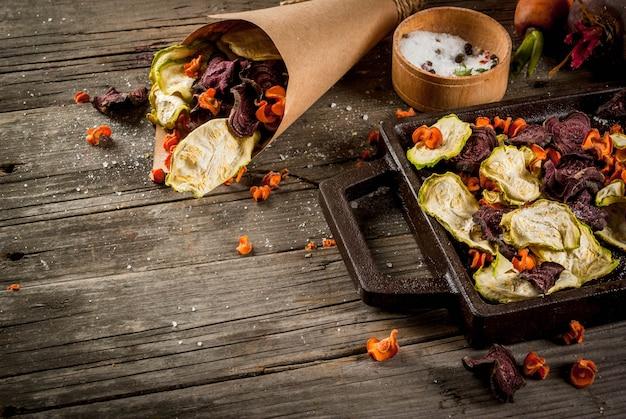 有機ダイエット食品。ビーガンダイエット。乾燥野菜。ビート、ニンジン、ズッキーニの自家製チップ。古い木製の素朴なテーブル、新鮮な野菜。コピースペース