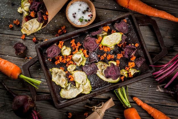 有機ダイエット食品。ビーガンダイエット。乾燥野菜。ビート、ニンジン、ズッキーニの自家製チップ。古い木製の素朴なテーブル、新鮮な野菜。上面図