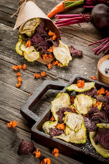 有機ダイエット食品。ビーガンダイエット。乾燥野菜。ビート、ニンジン、ズッキーニの自家製チップ。古い木製の素朴なテーブル、新鮮な野菜。